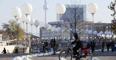 7nov2014---pedestres-passam-por-suportes-com-baloes-brancos-colocados-no-tracado-do-muro-de-berlim-na-capital-alema-a-instalacao-lichtgrenze-muro-de-luz-faz-parte-das-celebracoes-de-25-anos-da-1415363601440_956x500