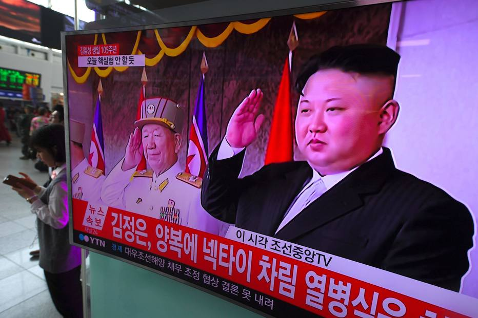 People walk past a television screen broadcasting live footage of a parade to mark the 105th anniversary of the birth of North Korea's founder Kim Il-Sung and showing North Korean leader Kim Jong-Un (R), at a railway station in Seoul on April 15, 2017. North Korean leader Kim Jong-Un on April 15 saluted as ranks of goose-stepping soldiers followed by tanks and other military hardware paraded in Pyongyang for a show of strength with tensions mounting over his nuclear ambitions. / AFP PHOTO / JUNG Yeon-Je